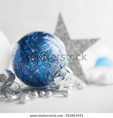 Blue and white xmas ornaments on glitter holiday background. Merry christmas card. Winter holidays. Xmas theme. Happy New Year. - stock photo