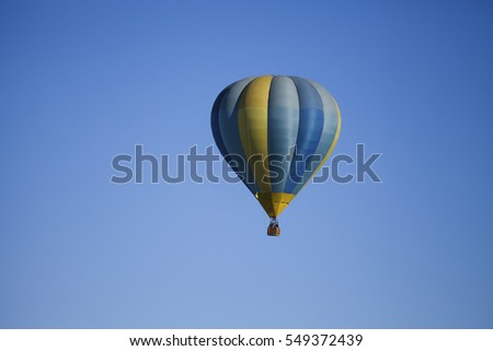 Blue and yellow balloon soaring in the sky