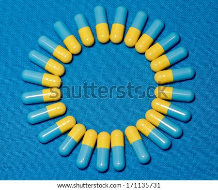 Blue and yellow capsules in a ring - stock photo