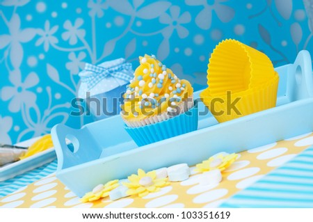 Blue and yellow cupcake setting on a platea - stock photo