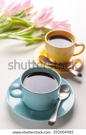 Blue and yellow cups of coffee with pink tulip on white background