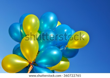 blue and yellow metallic balloons in the city festival on blue sky background - stock photo