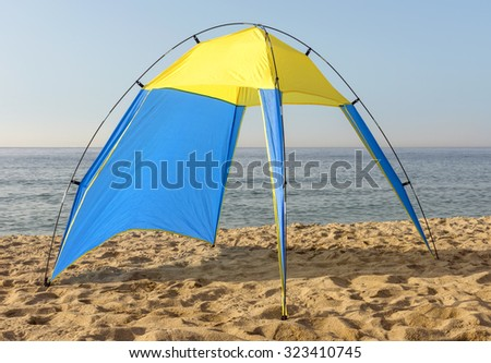 Blue and yellow nylon tent at the beach. - stock photo