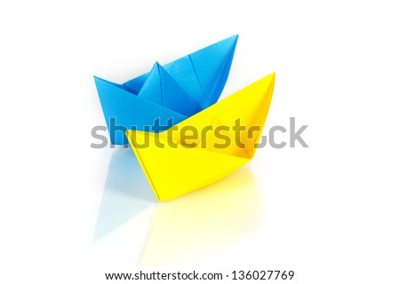 Blue and yellow paper ships on a glass with reflection