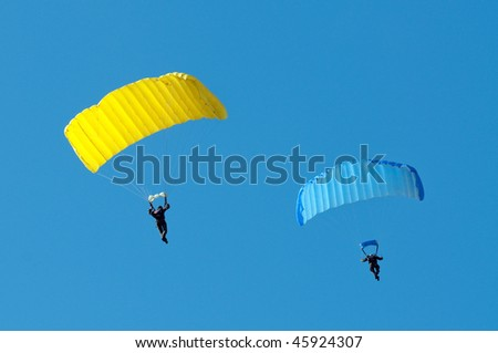 blue and yellow parachutists on clear blue sky