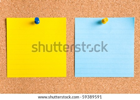 blue and yellow stripped notes attached by yellow and blue pins on cork board - stock photo