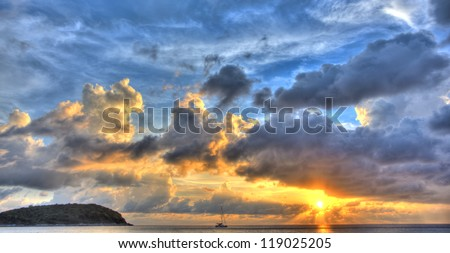 Blue and yellow sunset panorama over ocean with dramatic clouds with island and yacht - stock photo