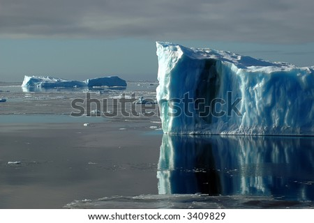 Blue Antarctic iceberg in the Southern Ocean on a nearly calm sea covered by ice floes. Some snow petrels are sitting on the top. Picture was taken during a 3-month research expedition. - stock photo