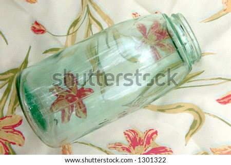 Blue antique glass jar used for canning fruits and vegetables,  sitting on a vintage table cloth. - stock photo