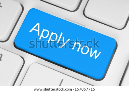 Blue apply now button on white keyboard close-up  - stock photo