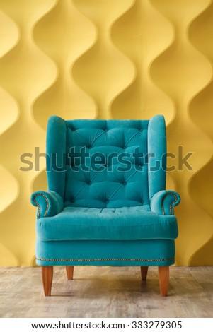 Blue armchair on yellow wall. Modern interior. Shallow DOF - stock photo