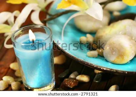 Blue aromatherapy candle and spa stones - stock photo