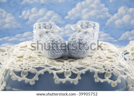 Blue baby booties for boy, horizontal with copy space, blue sky background with clouds, selective focus - stock photo