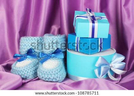 blue baby boots and gifts on silk background - stock photo