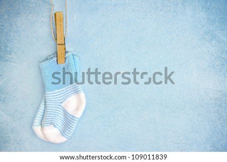 Blue baby socks on a textured rustic background with copy space - stock photo