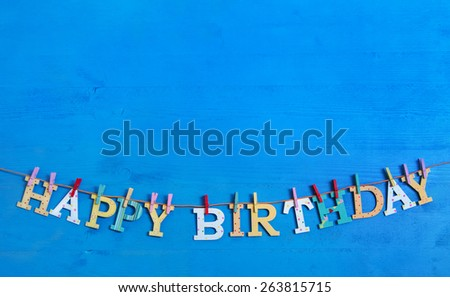 Blue background with colorful wooden hanging letters on a clothes line with text: happy birthday.