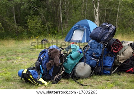 Blue backpacking bags piled up in a line at the campsite - stock photo