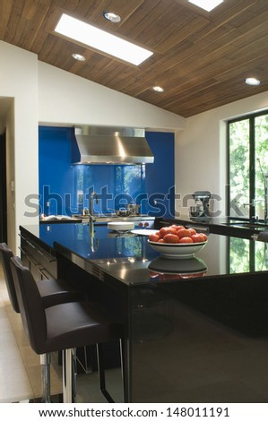 Blue backsplash and breakfast bar in modern kitchen - stock photo