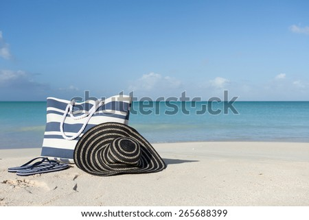 blue bag flip flops and hat on the beach - stock photo
