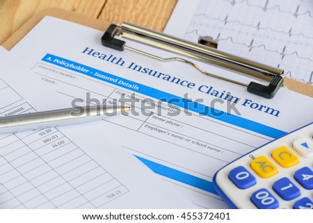 Blue ballpoint pen, a calculator and a health insurance claim form on a plywood clipboard. A blank form is waiting to be completed and signed by an insured person or a policyholder.