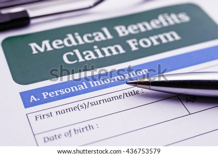 Blue ballpoint pen and a medical benefits claim form on a clipboard. A blank / empty form is waiting to be completed / filled and signed by a policyholder or an insured person. - stock photo