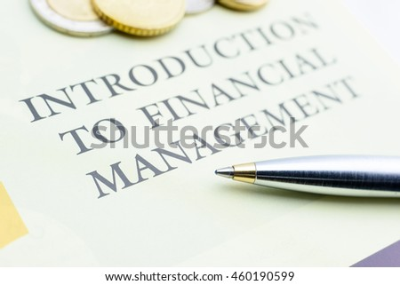 Blue ballpoint pen and coins on an introduction to financial management document. The basics that investors must learned or known before investing or putting money / cash in assets for optimal return.