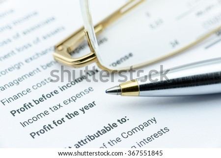 Blue ballpoint pen and eye grasses on a company's financial report, in the part of profit and net income. An analysis for a wealth and a long term sustainable investment concept. - stock photo