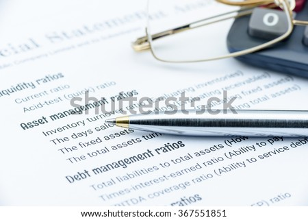 Blue ballpoint pen, eye glasses and a calculator on a paper of financial analysis check lists. Financial and investment analysis concept. - stock photo