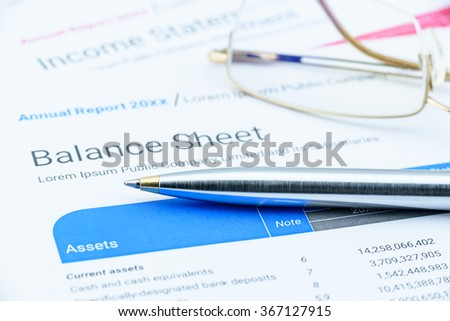 Blue ballpoint pen on a corporate balance sheet with eye glasses waiting for an auditor to audit before passing to executive committee in the boardroom. Financial and investment analysis concept. - stock photo