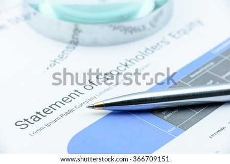 Blue ballpoint pen on a listed company's statement of stockholders' equity waiting for  brokers to check before passing to their majority shareholders. Financial and investment analysis concept. - stock photo