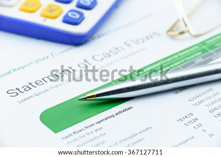 Blue ballpoint pen on a statement of cash flows with eye glasses and a calculator. Financial and investment analysis concept. - stock photo