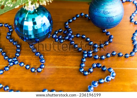 Blue balls on the Christmas tree and garlands on the wooden table - stock photo
