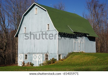 Blue Barn: A large wooden barn wears a subtle shade of blue on an autumn afternoon in Pennsylvania. - stock photo
