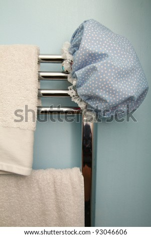 Blue bath hat on chrome radiator with white towels - stock photo