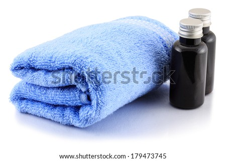 Blue Bath towel and bottles spa isolated on white background - stock photo