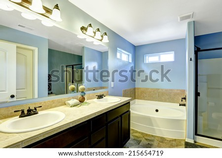 Blue bathroom with wooden cabinet, mirror and tile trim