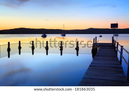 Blue bayou and jetty pool with perfect mirror reflections.  Yattalunga Australia at mid tide, dusk - stock photo