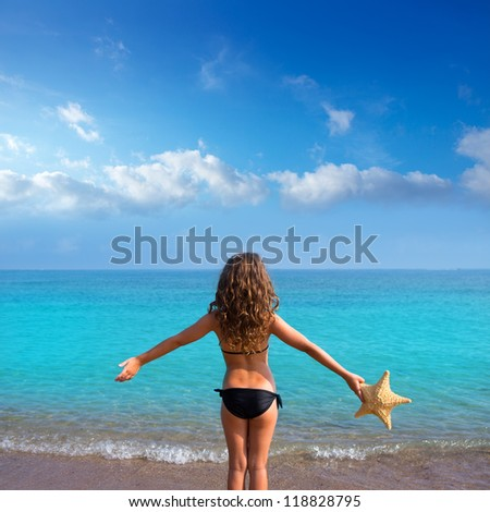blue beach kid girl with bikini holding starfish looking sea in rear view - stock photo