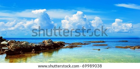 Blue beach landscape with Mediterranean sea & cloudy sky - stock photo