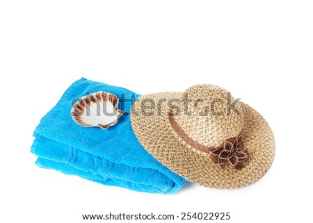 Blue beach towel with broad-brim straw summer hat and sea shell, isolated on white background - stock photo