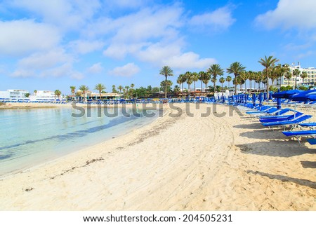 Blue beach umbrellas and sunbeds on Sandy Beach in Ayia Napa, Cyprus - stock photo