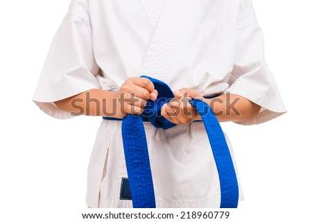 Blue belt. Little boy in kimono tying the knot to his black belt - stock photo