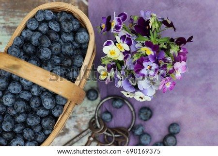 Blue berries in vintage basket, violet pansies, purple cloth on aged, weathered stool, daylight