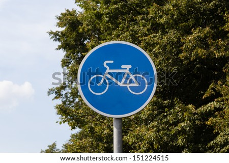 Blue bicycle lane sign with sky and trees background - stock photo