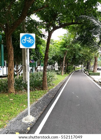 Blue bicycle lane sign ,with trees background.