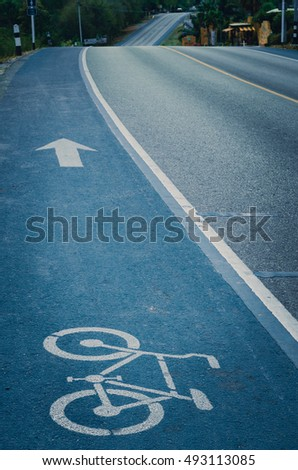 Blue bicycle lane signage on street, cinematic tone filter