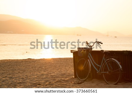 Blue bicycle standing on sandy beach during sunrise. Freedom and happiness concept. Old fashioned sepia colors. Post card view. - stock photo