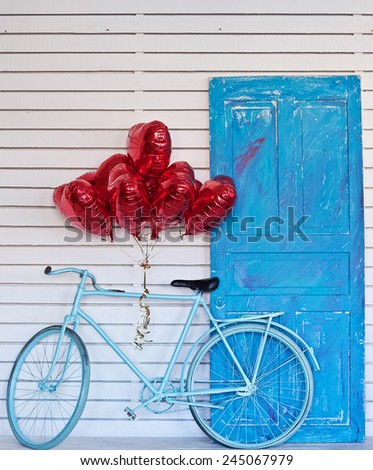 Blue bicycle with heart-shaped balloons. Valentine's day. - stock photo