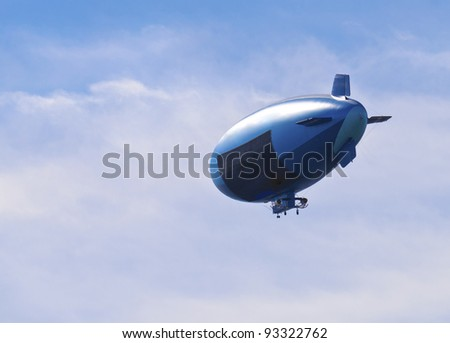Blue blimp in a blue and white sky with a black screen - stock photo