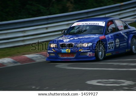 Blue bmw at height of curve in the evening - stock photo